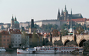 The Charles Bridge across Vltava River. Hrad (castle) and St. Vitus Dome (on top of castle mountain). Excursion boat.
