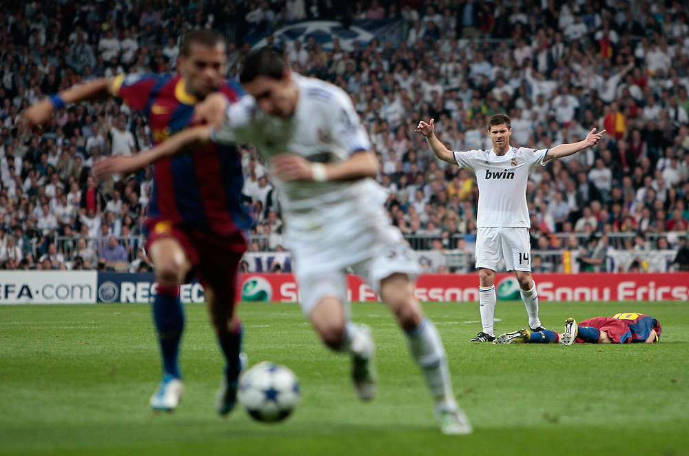 Real Madrid's Xabi Alonso, 2nd right, reacts while FC Barcelona Sergio Busquets, right, is on the ground during a semi final, 1st leg, Champions League soccer match against FC Barcelona at the Santiago Bernabeu stadium in Madrid, Wednesday, April 27, 2011.