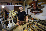"""LAMBERTVILLE, NJ - JUNE 02:  Adam Capone works on a sculpture in his studio June 2, 2014 in Lambertville, New Jersey.  Capone makes vivid sculptures from pieces of reclaimed wood, old furniture, etc. One of his most recent works is """"White Queen."""" (Photo by William Thomas Cain/Cain Images)"""