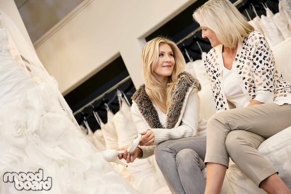 Happy mother and daughter sitting footwear in bridal store