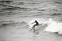 Luke Bartels carves on a wave with a wooden surfboard at Ocean Beach, San Francisco, on Wednesday, July 7, 2011.