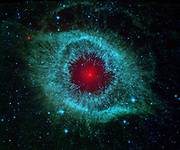 infrared image from NASA's Spitzer Space Telescope shows the Helix Nebula located about 700 light-years away in the constellation Aquarius, belongs to a class of objects called planetary nebulae. Planetary nebulae are the remains of stars that once looked a lot like the sun. When sun-like stars die, they puff out their outer gaseous layers. In Spitzer's infrared view of the Helix nebula, the eye looks more like that of a green monster's. Infrared light from the outer gaseous layers is represented in blues and greens. The white dwarf is visible as a tiny white dot in the center of the picture. The red color in the middle of the eye denotes the final layers of gas blown out when the star died. The brighter red circle in the very center is the glow of a dusty disk circling the white dwarf (the disk itself is too small to be resolved). This dust, discovered by Spitzer's infrared heat-seeking vision, was most likely kicked up by comets that survived the death of their star. Before the star died, its comets and possibly planets would have orbited the star in an orderly fashion.