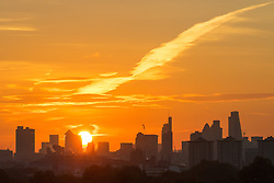 Primrose Hill, London, October 28th 2016. The autumn sun peeks from behind the skyscrapers of Docklands and The City as dawn breaks over London.