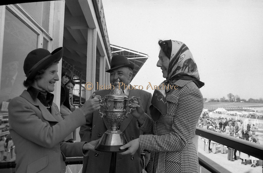 "Racing At Punchestown.     K22..1976..28.04.1976..04.28.1976..28th April 1976..The John Jameson Cup race was run today at Punchestown. The sponsor of the race are Irish Distillers Ltd. The race an extended handicap novice steeplechase is for horses four yers old and upwards that have not won a steeplechase on or before 1st Sept.,75..The race was won by ""No Hill"" owned by Mrs J.B.O'Callaghan,ridden by Mr T.M.Walsh and trained by Mr R Walsh..Image shows,Mrs F.J.O'Reilly, wife of the chairman at Irish Distillers presenting the cup to the owner of ""No Hill"", Mrs J.B.O'Callaghan (right) included in the photograph is Mr O'Callaghan."