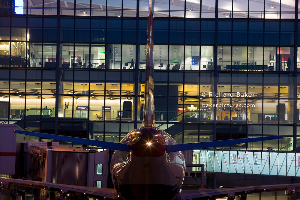 An exterior dusk view of a British Airways airliner parked at a gate at Heathrow Airport's Terminal 5 building  ..