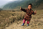 The exuberant young son of a yak herder suddenly appears roadside in the Phobjikha Valley [some call it the Gangte Valley] basin, Bhutan. The government and international conservation groups protect the valley because of its winter population of endangered black-necked cranes. From coverage of revisit to Material World 1994 book Project family in Bhutan, 2001.