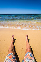 Legs and feet on a beach.  Haena Beach, Kauai, Hawaii.