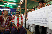 Karen refugees, both teenagers born in the camp and the war wounded hold placards telling the world of the plight of the Karen people during the Revolutionary Day service in Mae La camp.