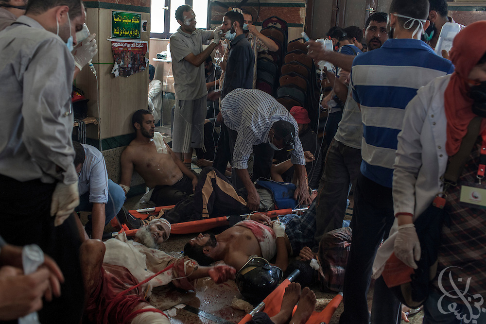A stream of wounded people are treated by overwhelmed emergency staff inside a packed field hospital at the Rabaah al-Adawiya protest camp in Nasr City during the August 14, 2013 Ministry of Interior/Police operation to clear the protest by force. The assault, which began at 7am with police moving in to seal the surrounding streets included tear gas and live fire, and there are reports of large numbers of killed and wounded protesters.