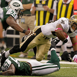 2009 October 04: New Orleans Saints running back Pierre Thomas (23) dives for extra yardage over New York Jets linebacker Bart Scott (57) during a 24-10 win by the New Orleans Saints over the New York Jets at the Louisiana Superdome in New Orleans, Louisiana.