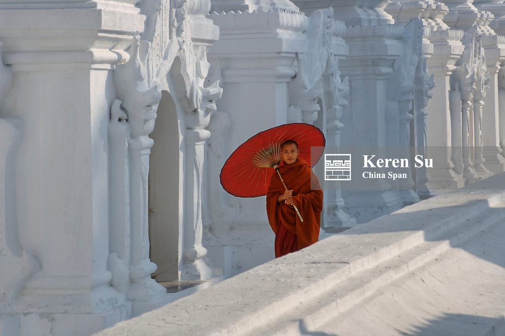 Monk with red umbrella with stupas at Sandamani Temple, Mandalay, Myanmar