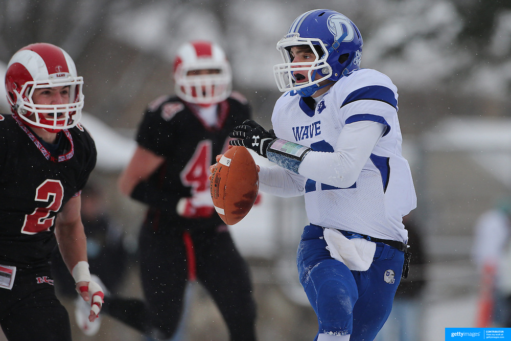 Darien quarterback Silas Wyper is challenged by Cole Harris, New Canaan, during the New Canaan Rams Vs Darien Blue Wave, CIAC Football Championship Class L Final at Boyle Stadium, Stamford. The New Canaan Rams won the match in snowy conditions 44-12. Stamford,  Connecticut, USA. 14th December 2013. Photo Tim Clayton
