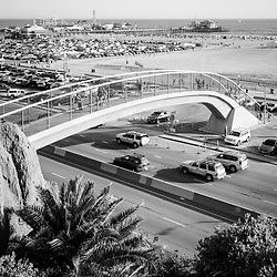 Santa Monica Beach pedestrian bridge and pier vertical black and white photo with Pacific Coast Highway. Copyright ⓒ 2017 Paul Velgos with All Rights Reserved.