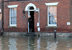 Boxing Day floods.. A resident  looks out from the front door of her flooded home in Yalding, Kent  as villagers   brace themselves for the possibility of more flooding with another storm on the way, Thursday, 26th December 2013. Picture by Stephen Lock / i-Images