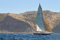 Sailboat by coastline on ocean