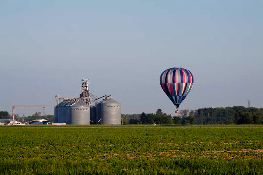 Hot air balloon floats by a grain elevator
