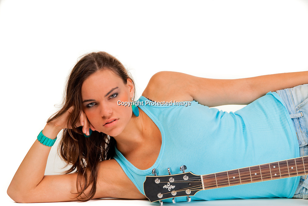 Female musician lying down with guitar, white background isolated