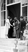 Emir Abdullah of Transjordan on the steps of  Government House, Jerusalem, 1921, shaking hands with Mrs Churchill, Winston Churchill standing next to his wife.