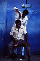 A man cuts the hair of another in the streets of Port-au-Prince Haiti.