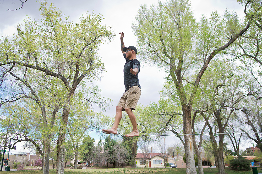 "mkb032317/metro/Marla Brose --  ""It's so much fun. It feels like you're floating,"" said Spencer Langefeld, after walking about 150 feet on a slack line that ran from two large budding oaks in Roosevelt Park, Thursday, March 23, 2017, in Albuquerque, N.M. Langefeld was one of a number of slack liners who frequent Roosevelt Park. The slack liners agreed that spring is one of the best times for the sport, except for the wind, which they said, makes balancing more challenging. (Marla Brose/Albuquerque Journal)"