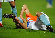 Robin Van Persie of Netherlands clutches his right ankle as he goes down injured during the friendly match with Italy.