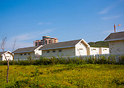 KUMGANG<br /> THE NORTH KOREAN GHOST TOWN<br /> <br /> The first town USA will find on his way to invade NK will be this ghost town where HUnday lost 1 billion USD..<br /> <br /> The Mount Kumgang tourist complex in North Korea, near the DMZ, was built in 1998 by the South Korean giant company Hyundai. The chaebol paid a fee of $1 billion to the North Korean government for 50 years of exclusivity. The cost of the 500-square kilometer complex was $400 million, including hotels, a spa, a fire station, a tourism office, a golf course, a supermarket, a clinic, tours in the mountain... Kumgang resort attracted nearly 2 millions south korean tourists from1998 to 2008.<br /> In July 2008 a South Korean tourist, Miss Park Wang-ja, was shot dead there and South Korea decided to stop all the tours in North Korea. The North Korean government said the tourist entered the military zone, and ignored the warnings from the north korean soldiers.<br /> So in retaliation, North Korea decided to seize the whole tourist complex. This decision was a real drama. Not for the touristic industry only, but for the separated families from the south and the north: Kumgang was also the place where hundreds of North and South Korean relatives were meeting each other for the first time in decades.<br /> For those reasons, since 2008, Mount Kumgang complex has became a ghost town. Only very few western tourists could visit the area.<br /> <br /> Photo shows:    Few houses are along the road. My guides explains that they have been seized by the North Korea government when South Korea did not keep its commitments. A classic way to rewrite History in North Korea!<br /> &copy;Eric Lafforgue/Exclusivepix Media