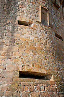 Stone building facade at Mont-Saint-Michel, France.  Highlights the wall fortifications and slits for the defenders.
