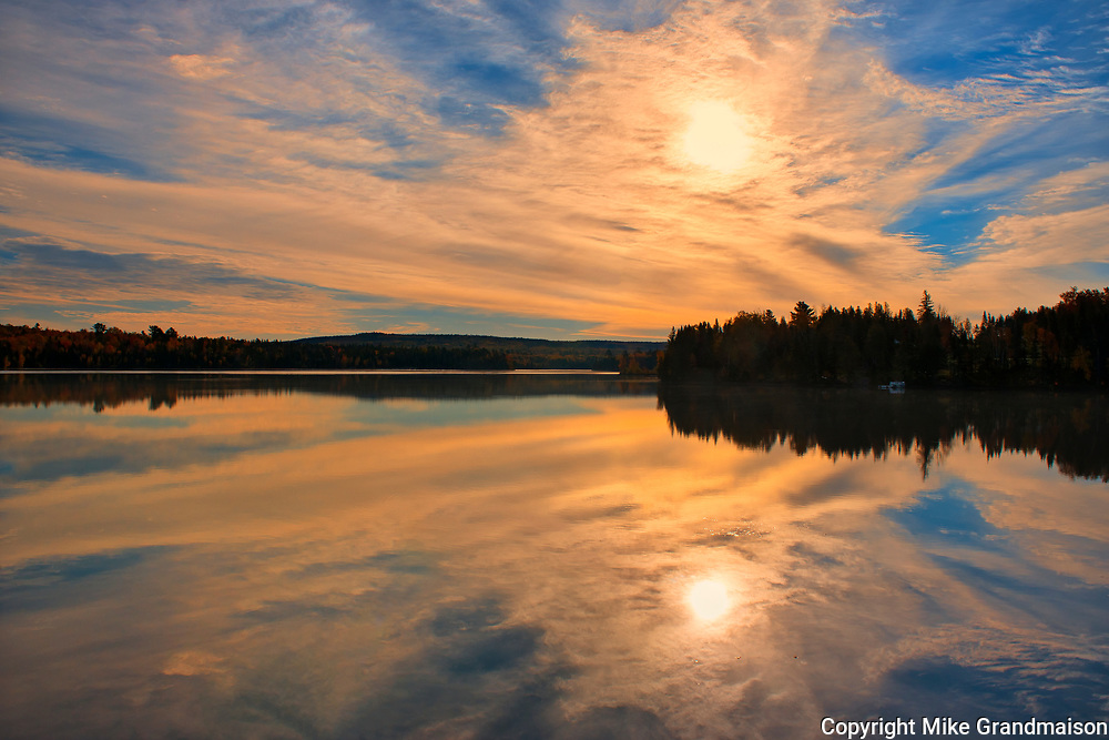 Clouds at sunrise reflected in the Saint John River <br />Mactaquac<br />New Brunswick<br />Canada