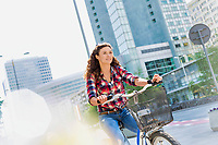 Portrait of young beautiful woman smiling while riding bicycle in the middle of the city