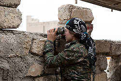 © Licensed to London News Pictures. 28/09/2014. Rabia, Iraq. A female fighter belonging to the Syrian-Kurdish YPJ scans Islamic State territory from a YPG position in the Iraqi border town of Rabia.<br /> <br /> Facing each other across the Iraq-Syria border, the towns of Al-Yarubiyah, Syria, and Rabia, Iraq, were taken by Islamic State insurgents in August 2014. Since then The town of Al-Yarubiyah and parts of Rabia have been re-taken by fighters from the Syrian Kurdish YPG. At present the situation in the towns is static, but with large exchanges of sniper and heavy machine gun fire as well as mortars and rocket propelled grenades, recently occasional close quarter fighting has taken place as either side tests the defences of the other. Photo credit: Matt Cetti-Roberts/LNP