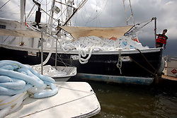 26 May 2010. Grand Isle, Lafourche Parish, Louisiana. <br /> From Barataria Bay to Grand Isle. The bay is devoid of life, no fishermen, no shrimp boats, even most of the birds have left. The environmental and economic impact is devastating with shrimp boats tied up, vacation rentals and charter boat fishing trips cancelled the only business for shrimpers is loading and laying boom and working for big oil. Oil from the Deepwater Horizon catastrophe is evading booms laid out to stop it thanks in part to the dispersants which means the oil travels at every depth of the Gulf and washes ashore wherever the current carries it. <br /> Photo credit; Charlie Varley<br /> www.varleypix.com