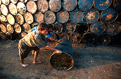 BANGLADESH CHITTAGONG MADHOM BIBIR HAT OCT00 - Labourers push oil-barrels filled with the remainder of ship diesel onto shore. It is one of the first activities once a new decommissioned ship has been beached...Several thousand labourers work on one medium-sized (50,000 ton) ship for a period of around three months, until it is completely dismantled and taken apart. ..Since Bangladesh does not possess mineral resources such as iron ore, it works out more cost-efficient to employ a large army of day-labourers to recycle the scrapped ships rather than to import ore. On average, a labourer can expect to earn a little more than 1 US Dollar per day...jre/Photo by Jiri Rezac..© Jiri Rezac 2000..Contact: +44 (0) 7050 110 417.Mobile: +44 (0) 7801 337 683.Office: +44 (0) 20 8968 9635..Email: jiri@jirirezac.com.Web: www.jirirezac.com..© All images Jiri Rezac 2000 - All rights reserved.