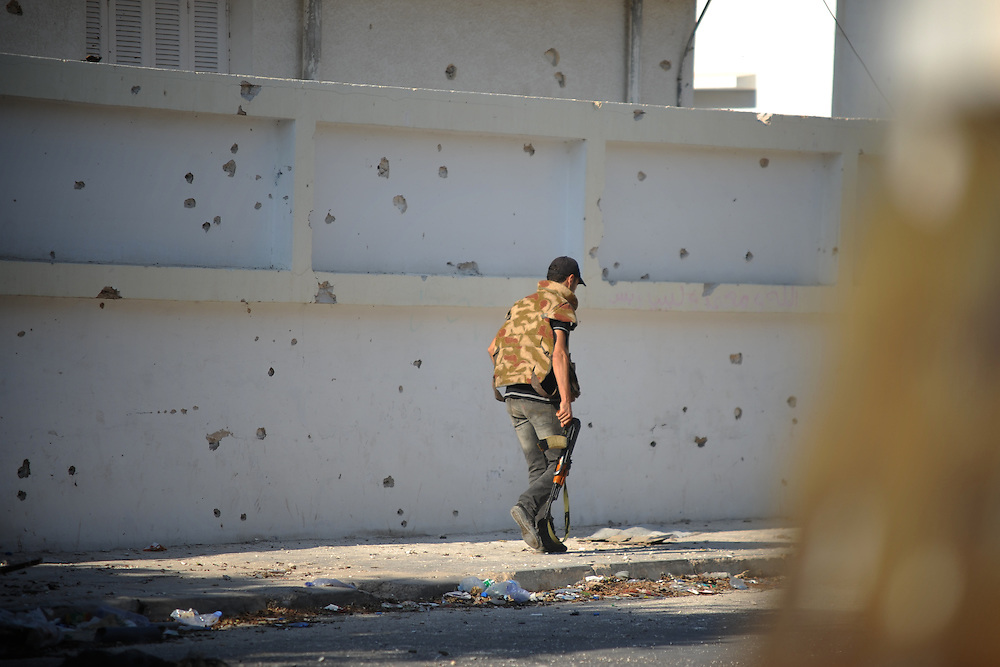 A rebel fighter passes by a partially destroyed wall in central Zawiyah.