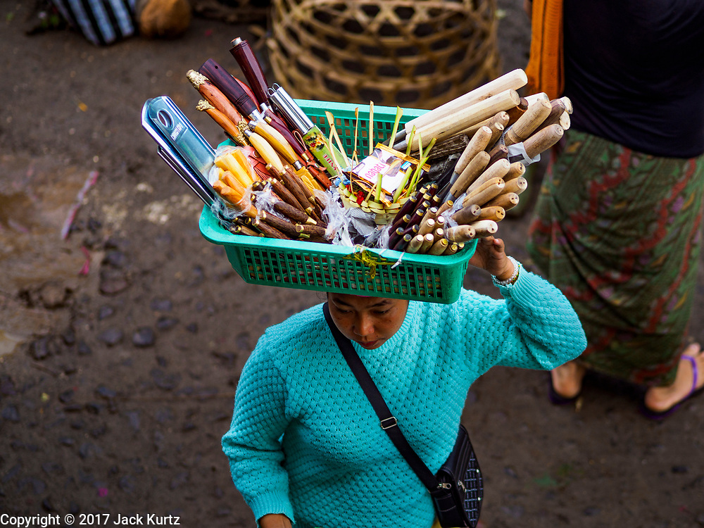 04 AUGUST 2017 - PAYANGAN, BALI, INDONESIA: A cutlery vender walks through the local market in Payangan, about 45 minutes from Ubud. Bali's local markets are open on an every three day rotating schedule because venders travel from town to town. Before modern refrigeration and convenience stores became common place on Bali, markets were thriving community gatherings. Fewer people shop at markets now as more and more consumers go to convenience stores and more families have refrigerators.      PHOTO BY JACK KURTZ