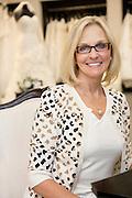 Portrait of a happy senior woman wearing eyeglasses sitting in bridal boutique