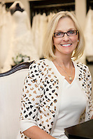 Portrait of a happy senior woman wearing eyeglasses sitting in bridal boutique
