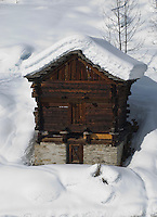 Ticino, Southern Switzerland. Typical, local, traditional, stone-based, wooden, storage hut covered in wintry snow.