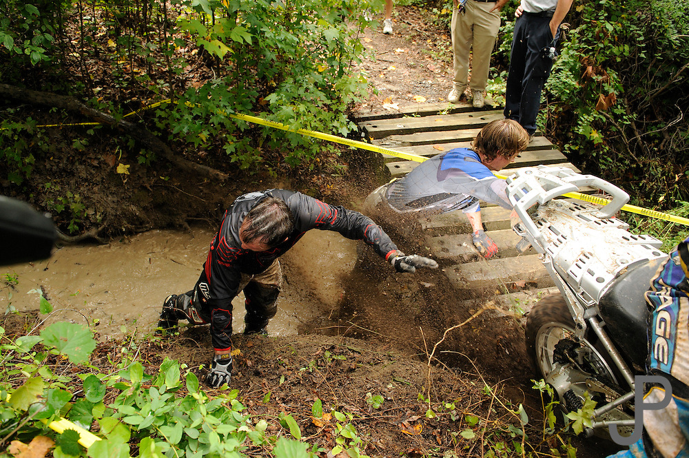 Bill Dragoo and Brad ? dodge mud from the back tire of a BMW R1200GS they had just pushed out of a wet creek bed at the BMW GS Trophy Challenge in Spartanburg, SC.