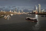 Looking eastwards (downriver) from Waterloo Bridge to the Southbank and the City of London, a burst of sunlight shines across river traffic, from the top of the One Blackfriars skyscraper, on 4th March 2019, in London England.