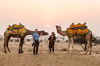 a Caucasian couple posing with two camels on a sand dune in the Thar Desert, Rajasthan, India.