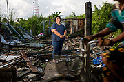 Nutchanart Thanthong stands in the remains of a destroyed house in the small slum community fighting forced evictions. For over 20 years she has assisted communities in and around Bangkok who are facing eviction.