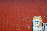 Blue Sunoco gas pump against red wall