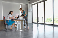 Two women discussing document at desk in empty office building