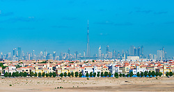 Skyline of Dubai with modern luxury villas at The Villa residential housing development in foreground in United Arab Emirates