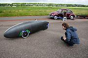 Daniel Fenn bekijkt de driewielige Cygnus. Het Nederlandse team van Cygnus test op de testbaan van de RDW in Lelystad de fiets waarmee ze een record willen gaan rijden.<br /> <br /> Daniel Fenn is watching the Cygnus trike. Team Cygnus is testing their bike to break the world record at the test track in Lelystad.