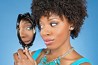 Close-up of African American woman looking at herself in mirror over colored background