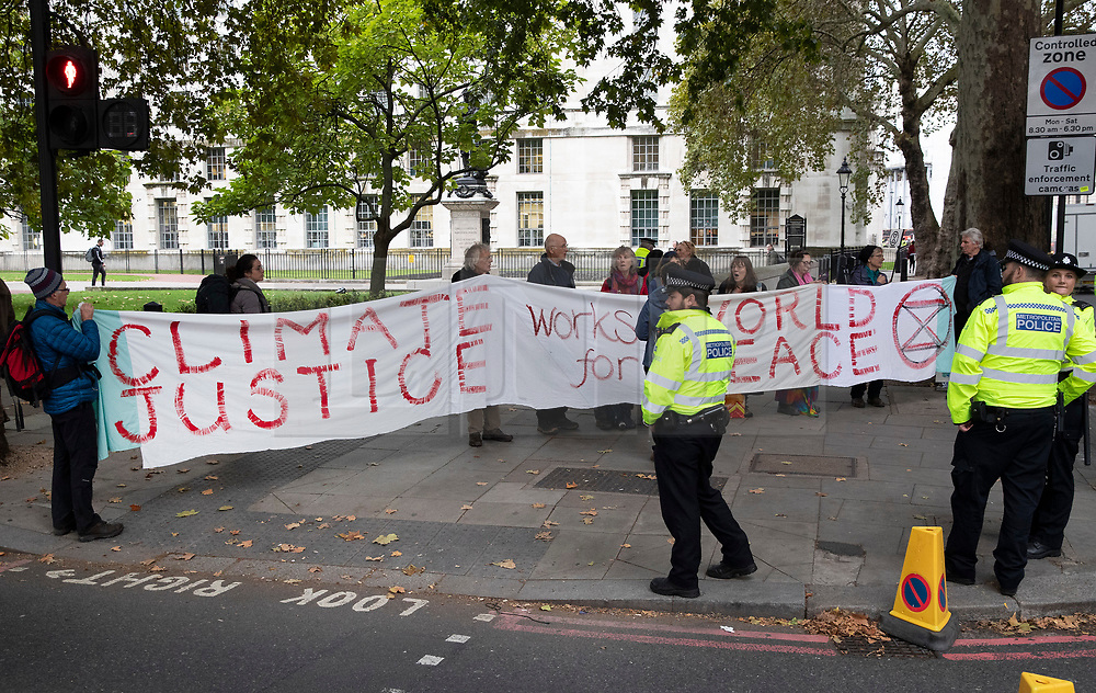© Licensed to London News Pictures. 07/10/2019. London, UK. Extinction Rebellion protestors are surrounded by police as they stand on Embankment near the Ministry of Defence in central London . Activists will converge on Westminster blockading roads in the area for at least two weeks calling on government departments to 'Tell the Truth' about what they are doing to tackle the Emergency. Photo credit: Peter Macdiarmid/LNP
