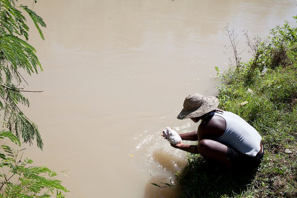 A woman does her laundry in the Artibonite River, the source of the recent cholera outbreak, on Sunday, October 31, 2010 in Petite Riviere, Haiti.