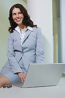 Business woman using laptop indoors