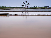 09 MARCH 2015 - NA KHOK, SAMUT SAKHON, THAILAND: A windmill is used to control the flow of sea water through evaporation ponds on a salt farm in Thailand. The coastal provinces of Samut Sakhon and Samut Songkhram, about 60 miles from Bangkok, are the center of Thailand's sea salt industry. Salt farmers harvest salt from the waters of the Gulf of Siam by flooding fields and then letting them dry through evaporation, leaving a crust of salt behind. Salt is harvested through dry season, usually February to April. The 2014 salt harvest went well into May because the dry season lasted longer than normal. Last year's harvest resulted in a surplus of salt, driving prices down. Some warehouses are still storing salt from last year. It's been very dry so far this year and the 2015 harvest is running ahead of last year's bumper crop. One salt farmer said prices are down about 15 percent from last year.    PHOTO BY JACK KURTZ